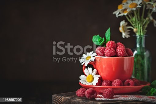499658564istockphoto Raspberry in a red cup with chamomile and leaves on a dark background. Summer and healthy food concept. Background with copy space. Selective focus. 1163557207