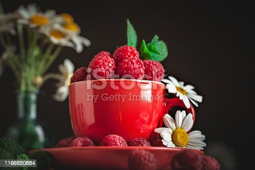 499658564istockphoto Raspberry in a red cup with chamomile and leaves on a dark background. Summer and healthy food concept. Selective focus. 1166650884