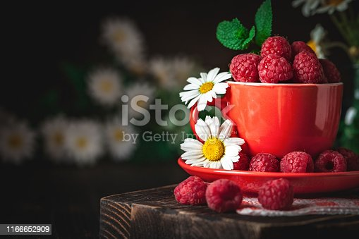 499658564istockphoto Raspberry in a red cup with chamomile and leaves on a dark background. Summer and healthy food concept. Background with copy space. Selective focus. 1166652909