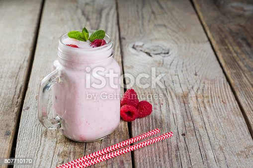 648804276 istock photo Raspberry jogurt smoothie in glass jar 807710170