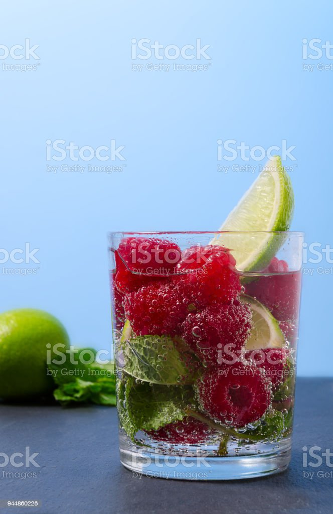 Raspberry lemonade with lime and mint in a glass. Non-alcoholic raspberry refreshment drink. Raspberry mojito in a glass with mint and lime. stock photo
