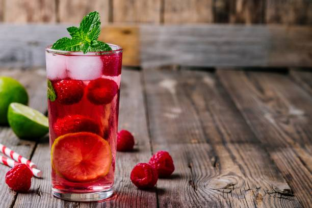 Raspberry Mojito Lemonade with lime and fresh mint in glass on wooden background stock photo