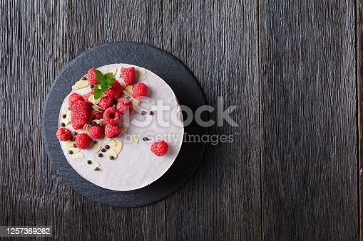 raspberry mousse cake on a slate black plate on a dark wooden table, landscape view from above, flat lay, free space
