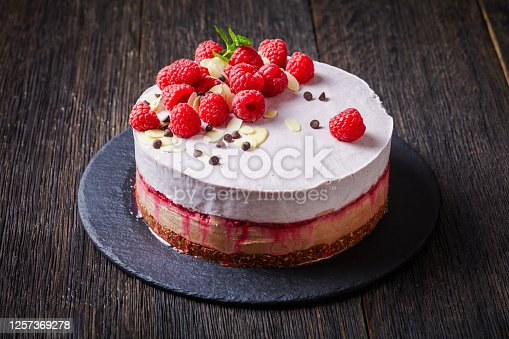 close-up of raspberry ice cream cake on a slate black plate on a dark wooden table, landscape view from above