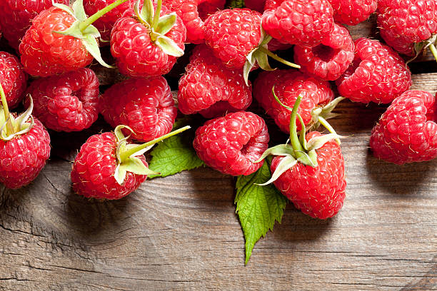raspberry on old wooden table - xxmmxx stock photos and pictures