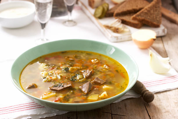 Rassolnik, traditional Russian soup, served with various snacks and vodka. Rustic style. stock photo