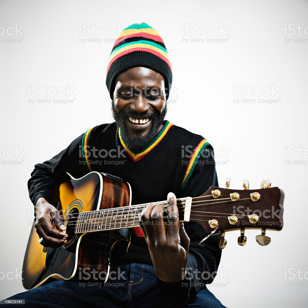 Rastafarian Man Playing guitar stock photo