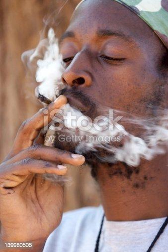 182677415 istock photo Rastafarian man smoking marijuana 139980505