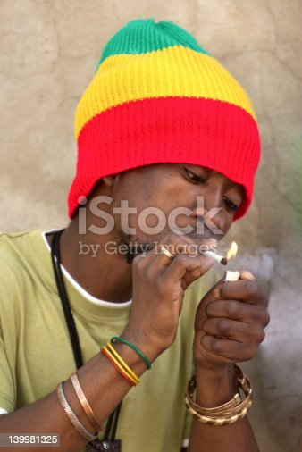 182677415 istock photo Rastafarian man smoking marijuana 139981325