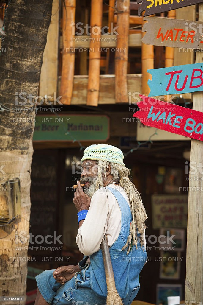 Rastafarian old man smoking a cigar stock photo