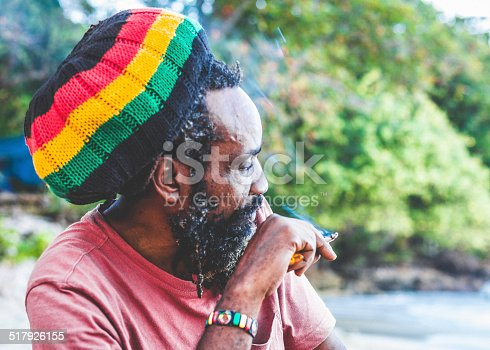Senior rastaman smoking at the beach.