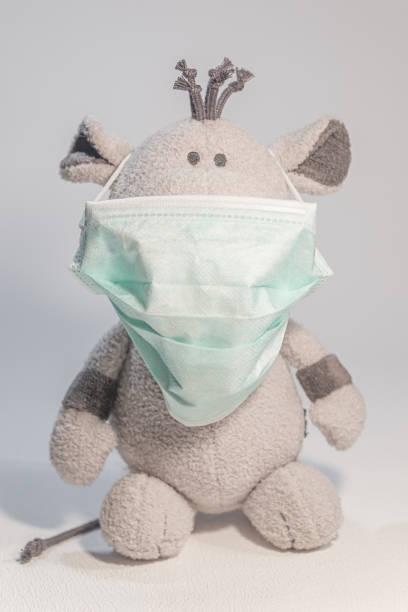 Ratte Kuscheltier trägt eine medizinische Gesichtsmaske als Symbol für Coronavirus-Epidemie Ausbruch in China bei Rat Year von chinesischen Sternzeichen Kalender, Details, Nahaufnahme – Foto