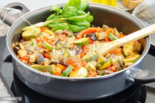 Mediterranean-style vegetable stew called traditional french ratatouille with freshly mixed vegetable in a cooking pan on a black induction heater
