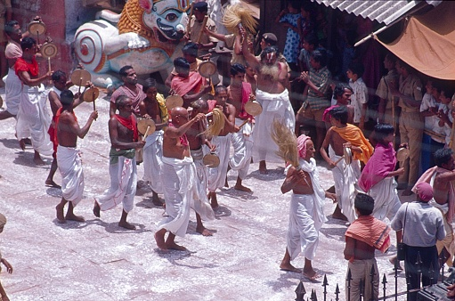 Kanchipuram, Tamil Nadu, India, 1974. Rathotsavam Festival. Hindu procession and temple chariot to bring the divine to earth and mingle with people. Furthermore: believers, spectators and law enforcement officers.