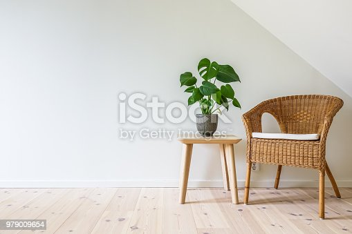 istock Rattan armchair with a wooden table with a potted plant 979009654