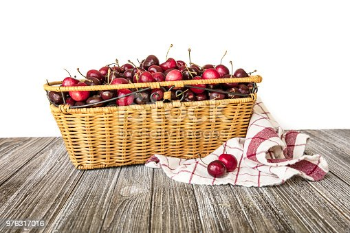 istock Rattan basket filled with sweet red Bing cherries white background 976317016
