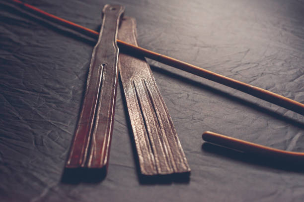 rattan cane and leather tawse for punishment - sculacciate foto e immagini stock