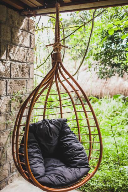 rotan rieten stoel met zwart kussen opknoping in de tuin, zomer - schommelen bungelen stockfoto's en -beelden