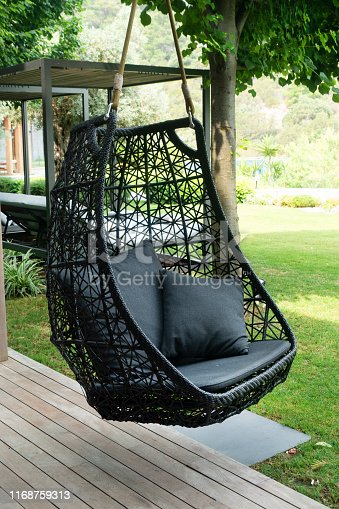 Rattan oval hanging chair with  pillow in tropical plant