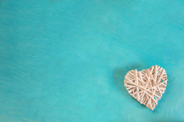 Rattan Woven White Decorative Heart on Painted Turquoise Background Corner Position. Valentine Mother's Day Romantic Greeting Card Banner Poster. Kids Charity Concept Copy Space stock photo