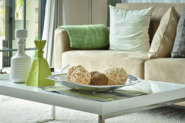 ratten bälle und vasen auf tisch mit hellem braun sofa - kissen grün stock-fotos und bilder