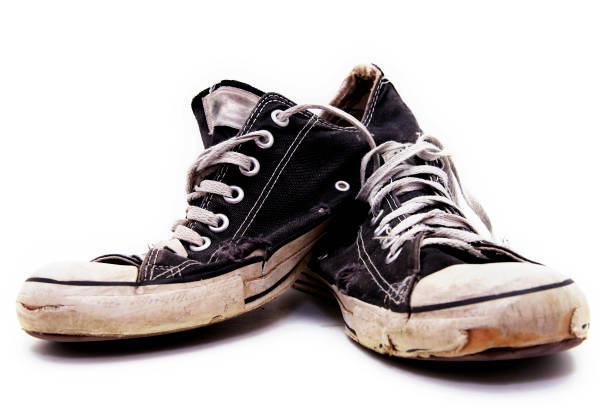 ratty, old pair of black converse sneakers - dirty shoes stock photos and pictures