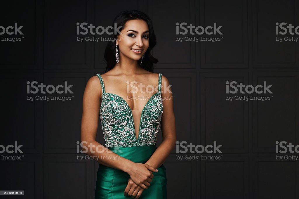 raven haired indian lady posing in studio against gray wall stock photo