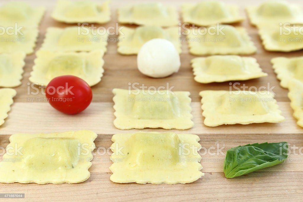 Ravioli arranged in a row with tomato, bocconcini and basil stock photo