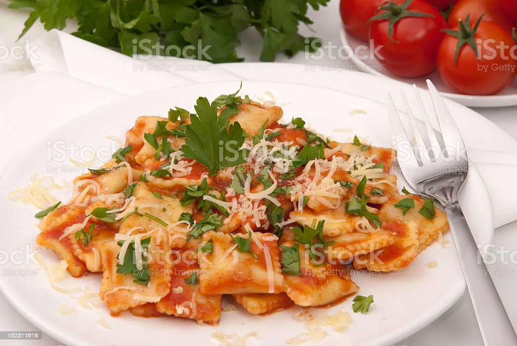 Ravioli in tomato sauce with fork on white plate stock photo