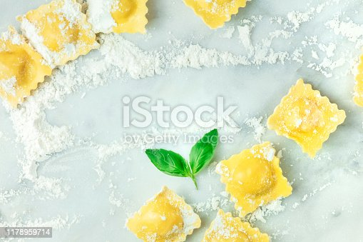 istock Ravioli with flour and basil leaves, forming a frame, shot from the top on a white marble background with a place for text, a design template 1178959714