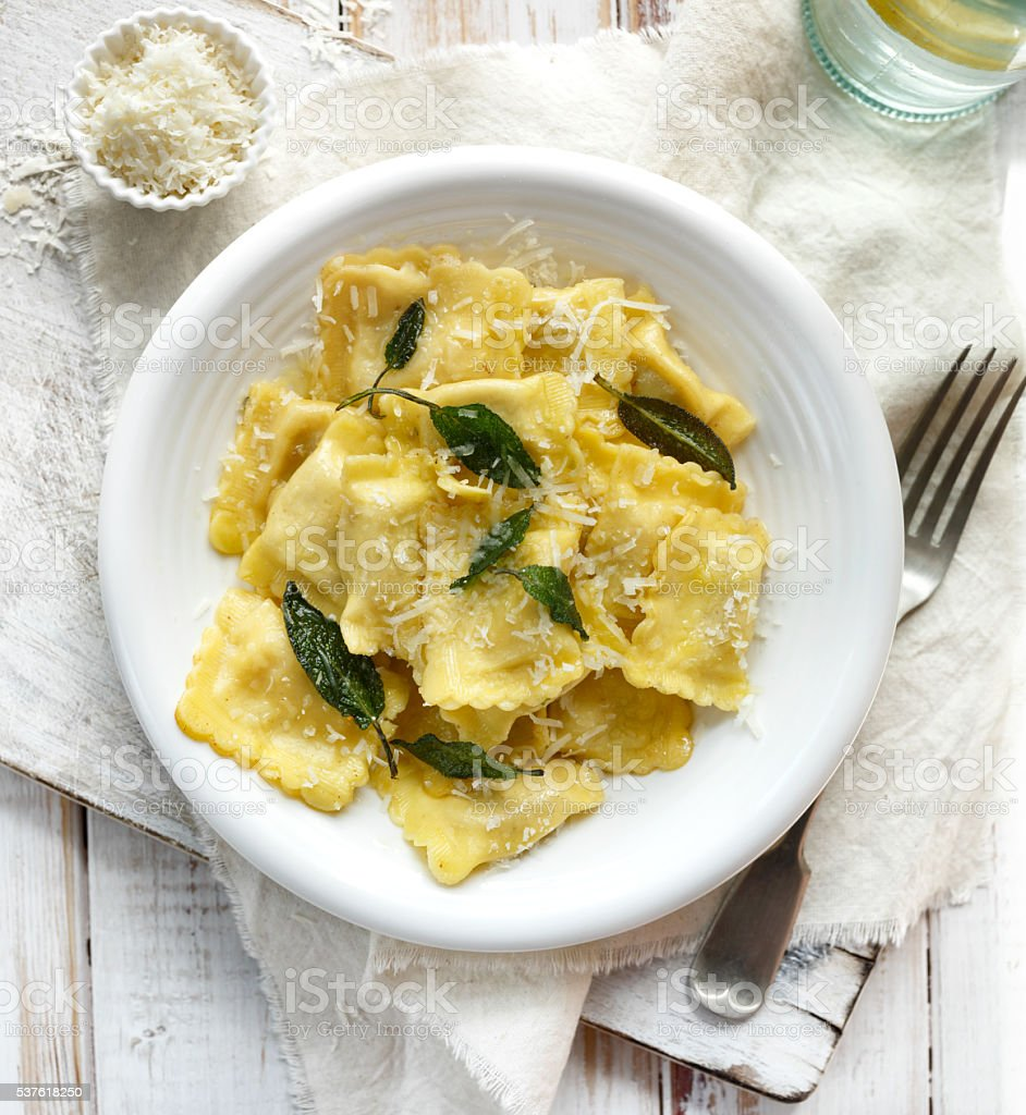 Ravioli with sage butter sprinkled with grana padano cheese stock photo