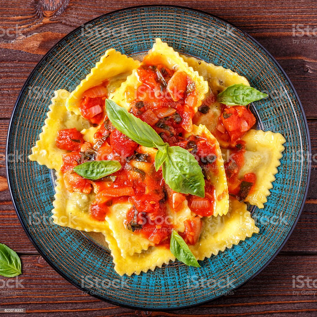 Ravioli with tomato sauce and basil on dark background. stock photo