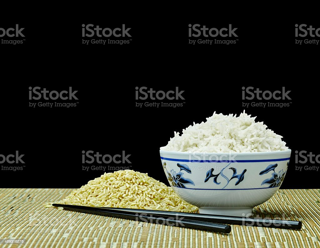 Raw and Cooked Organic Rice with Chopsticks on Black Background stock photo