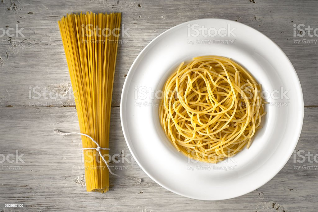 Raw and cooked spaghetti on  white wooden table top view – Foto
