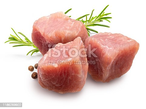 Raw and fresh (diced) pieces of turkey meat (chicken). With branch of rosemary and pepper (spices). Isolated on white background.
