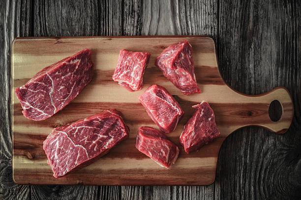 Raw angus beef slices on the wooden board top view Raw angus beef slices on the wooden board top view horizontal beef bourguignon stock pictures, royalty-free photos & images