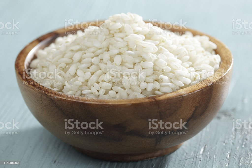 Raw arborio rice in bamboo bowl stock photo