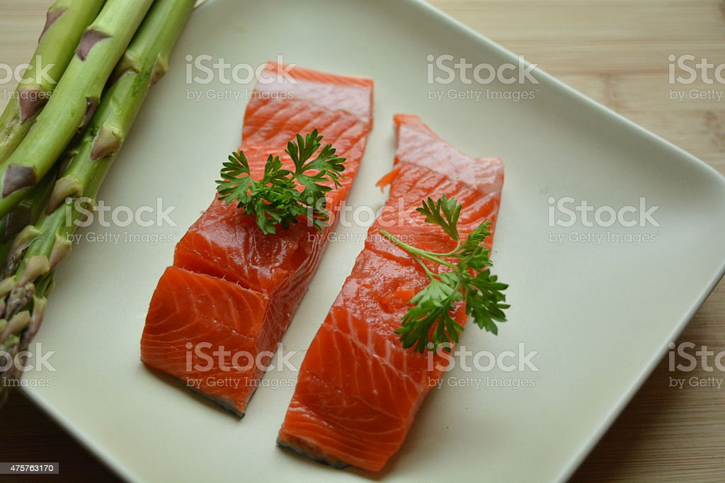 Raw asparagus and salmon garnished with parsley stock photo