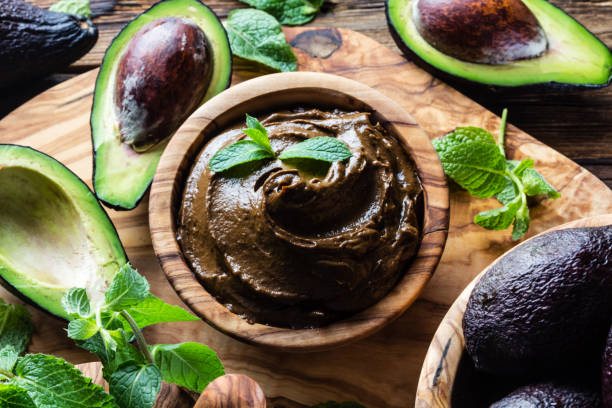 Raw avocado chocolate mousse pudding with mint in olive wooden bowl. Vegan vegetarian food. Organic healthy dessert. Raw avocado chocolate mousse pudding with mint in olive wooden bowl. Vegan vegetarian food. Organic healthy dessert pudding stock pictures, royalty-free photos & images