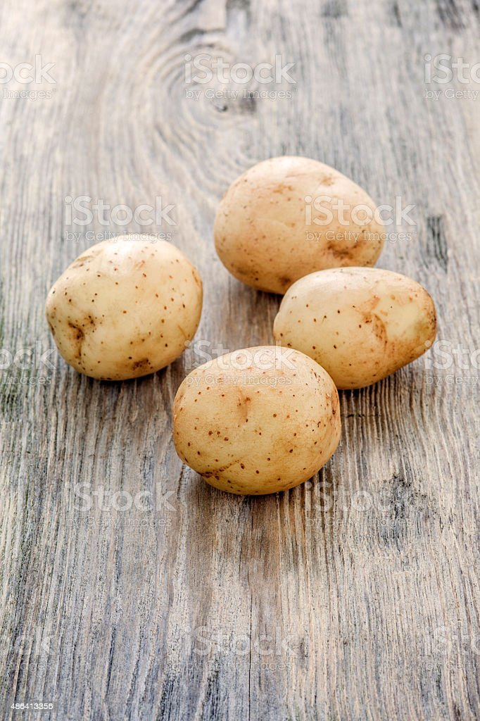 raw baby potatoes on wooden background stock photo