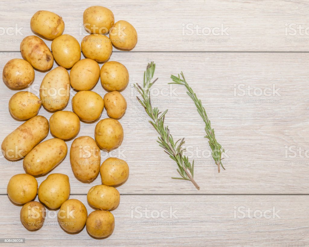 raw baby potatoes with rosemary on rustic wooden background, top view stock photo