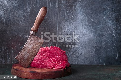 Raw beef meat cleaver on chopping deck on rust background with copy space
