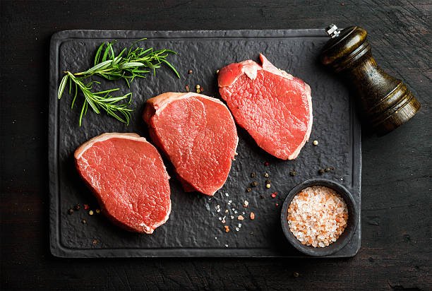 Raw beef Eye Round steaks with spices and rosemary stock photo