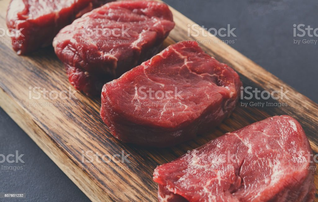 Raw beef filet mignon steaks on wooden board at gray background stock photo