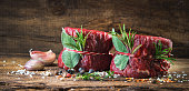 Raw beef fillet steaks mignon on wooden background