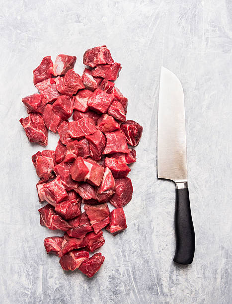 Raw beef goulash meat diced for stew with  knife stock photo