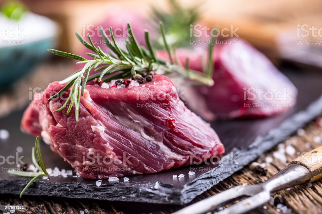 Raw beef meat. Raw beef tenderloin steak on a cutting board with rosemary pepper salt in other positions stock photo