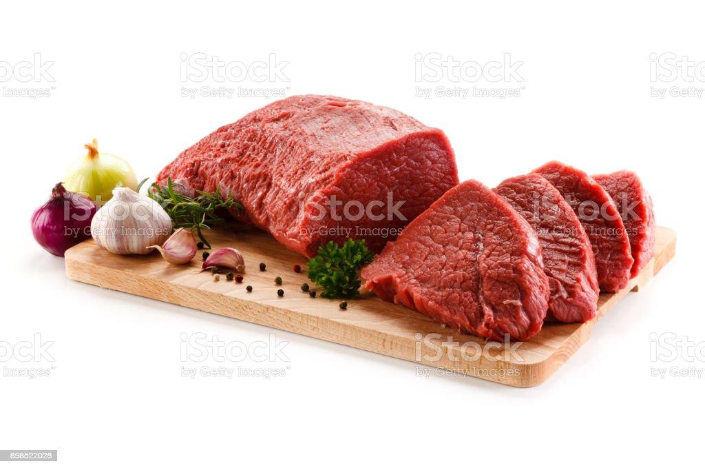 Rohes Rindfleisch auf Schneidebrett und Gemüse – Foto