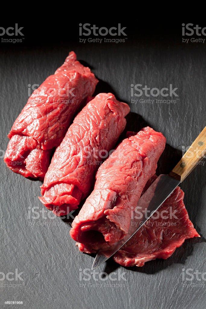 Carne crua roulades e faca em ardósia - foto de acervo