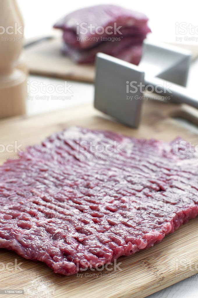Raw beef round steak and pounder royalty-free stock photo